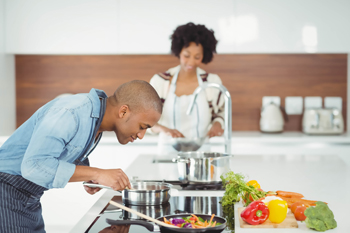 A couple cooking vegetables