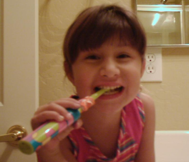 Isabelle G in Arizona brushing her teeth using her electric toothbrush - Age 5