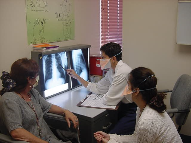 Masked doctors and patient discussing exam and patient xrays